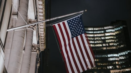 American Flag In Front Of A Building At Night