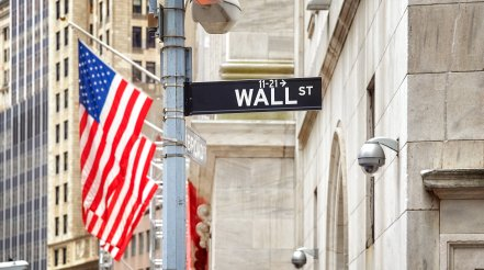 Wall Street Sign With American Flag In Distance, NYC, USA.